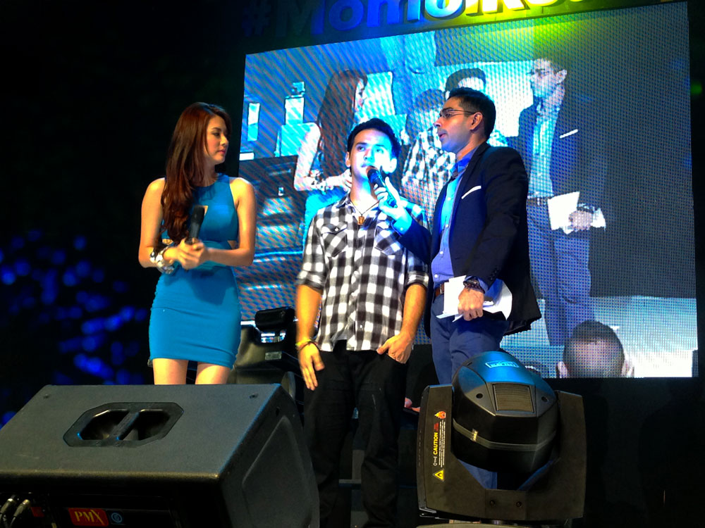 The After pic of Eo Marcos, onstage at the event accompanied by Jinri Park and Sam YG